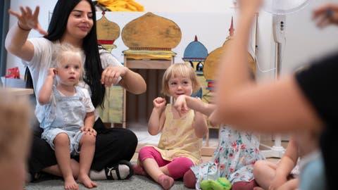 Kleinkinder sitzen gemeinsam mit Betreuerinnen in einer Kita im Kreis. (Bild: Keystone/Gaetan Bally)