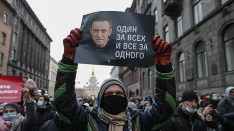 epa08959951 A protester holds a poster that reads 'One for all and all for one', during an unauthorized protest in support of Russian opposition leader and blogger Alexei Navalny, in St. Petersburg, Russia, 23 January 2021. Navalny was detained after his arrival to Moscow from Germany on 17 January 2021. A Moscow judge on 18 January ruled that he will remain in custody for 30 days following his airport arrest. Navalny urged Russians to take to the streets to protest. In many Russian cities mass events are prohibited due to an increasing number of cases of the COVID-19 pandemic caused by the SARS CoV-2 coronavirus.  EPA/ANATOLY MALTSEV (Anatoly Maltsev / EPA)