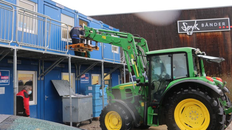 Umzugshelferhieven das Mobiliar aus dem Containerbau auf einePalette, die auf der Gabel eines Traktors steht. (Dennis Kalt)