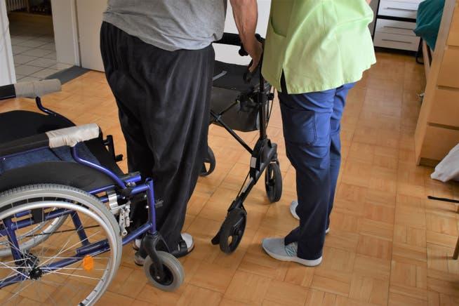 Spitex-Mitarbeiterin Silvia Böni begleitet den Kunden mit dem Rollator ins Badezimmer.