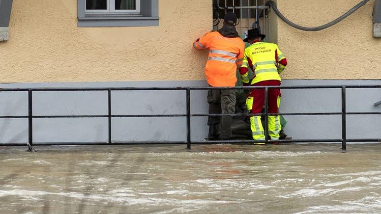 Hochwasser-Einsatz im Juli: Zivilschutz und Feuerwehr deponieren Sandsäcke vor dem Eingang eines Wohnhauses in Mellingen. (Alexandra Wey / KEYSTONE)