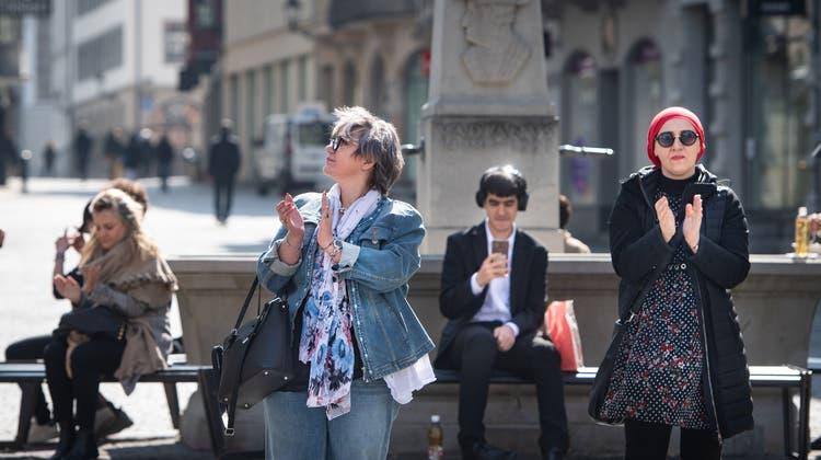 Passanten in der St.Galler Altstadt bedanken sich mit einem schweizweit koordinierten Applaus bei Ärztinnen und Pflegerinnen, die im Einsatz gegen die Coronapandemie stehen. (Benjamin Manser)
