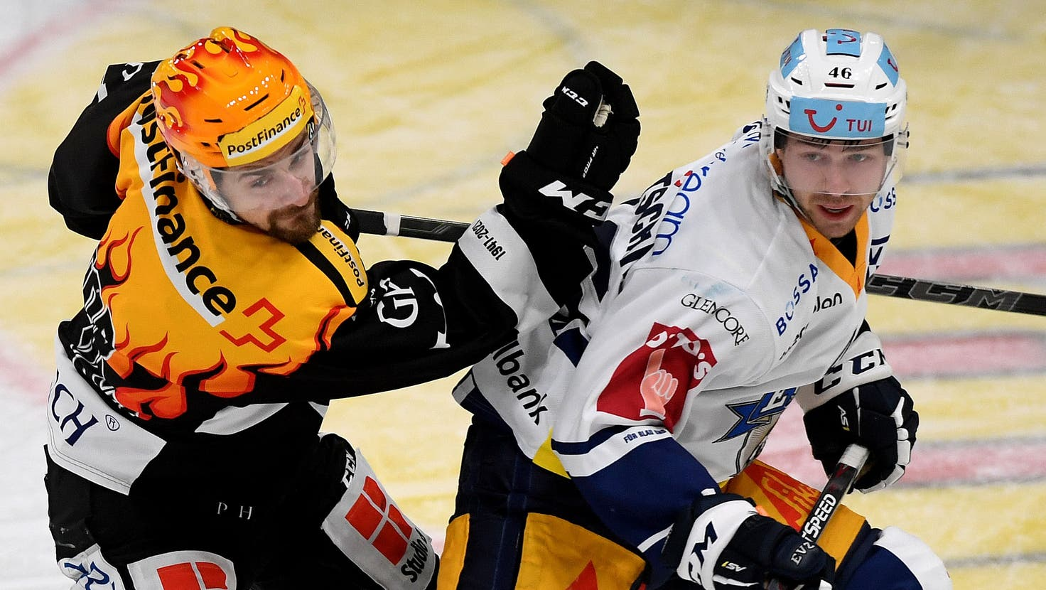 Lugano's Top Scorer Mark Arcobello, left, fights for the puck with Zug's player Lino Martschini, during the preliminary round game of National League Swiss Championship between HC Lugano and EV Zug, at the Corner Arena stadium in Lugano, on Friday, 15 January 2021. (PostFinance/KEYSTONE/Ti-Press/Samuel Golay) (Samuel Golay / KEYSTONE/TI-PRESS)