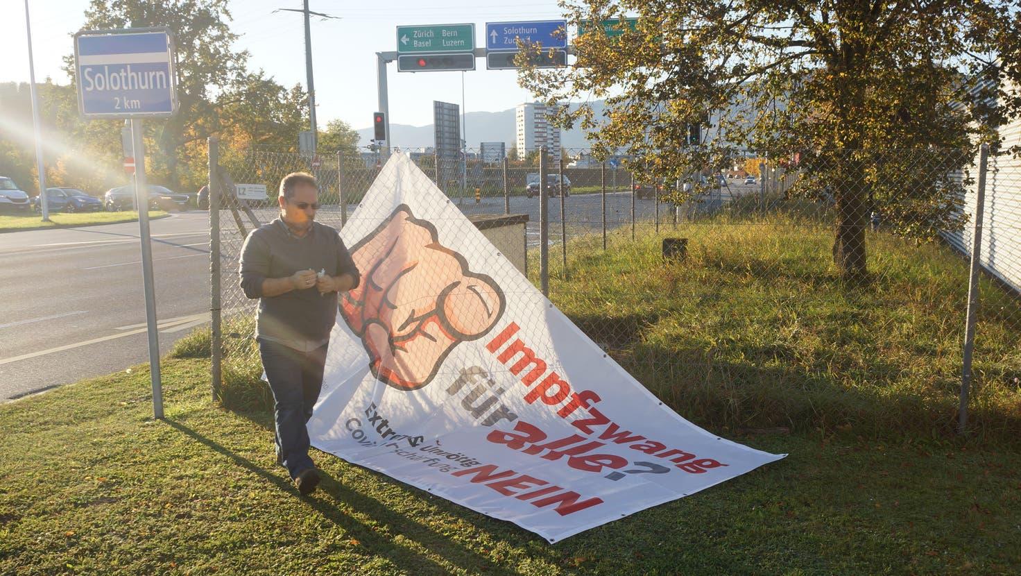 Carlo Rüsics, SVP Gemeinderat und Mitglied der «Freunde der Verfassung» hängt das Banner erneut an der Stelle auf, wo es von der Polizei entfernt wurde. (Urs Byland)