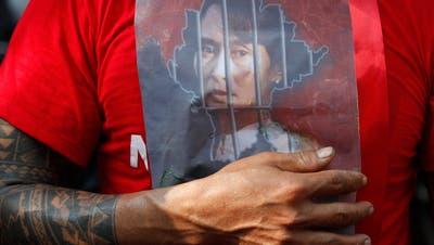 Ein Demonstrant mit Bild der abgesetzten De-facto-Regierungschefin Aung San Suu Kyi: Vor mehreren Botschaften im Ausland, hier in Bangkok, protestierten Menschen gegen den Militärputsch in Myanmar. (Rungroj Yongrit / EPA)