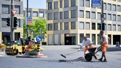 Asphalt ist nicht gleich Asphalt: Ein hellerer Belag heizt an einem Sommertag weniger auf als ein pechschwarzer Strassenbelag. Bauarbeiter machen den Belag an der St.Leonhardsstrasse neu. Im Hintergrund das «Leopard»-Gebäude. (Bild: Urs Jaudas (11. Juli 2010))