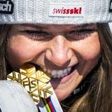 Ist sie wirklich echt? Corinne Suter beisst in die Goldmedaille. (Jean-Christophe Bott / KEYSTONE)
