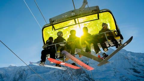Skifahrer auf einem Sessellift in Wengen. (Bild: Jean-Christophe Bott / Keystone)