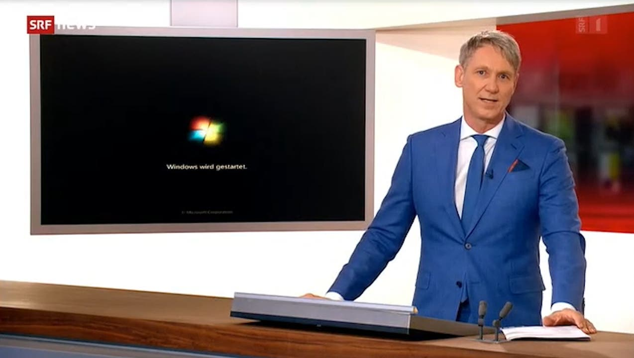 Während Franz Fischlin moderiert, startet im Hintergrund das System neu. SRF scheint noch mit Windows 7 zu arbeiten. (Screenshot SRF)