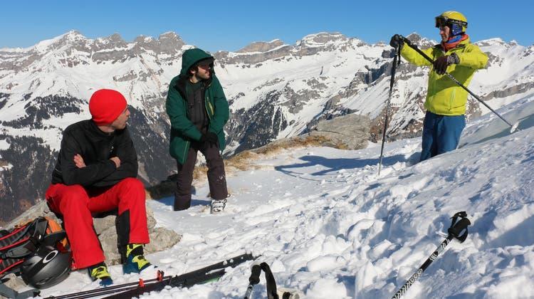 Bergführer Lucas Iten erklärt Tom (links) und Moritz, wie man mit Hilfe eines Skistocks die Steilheit eines Hangabschnitts berechnen kann. (Bild: Kristina Gysi (Engelberg, 21. Februar 2021))