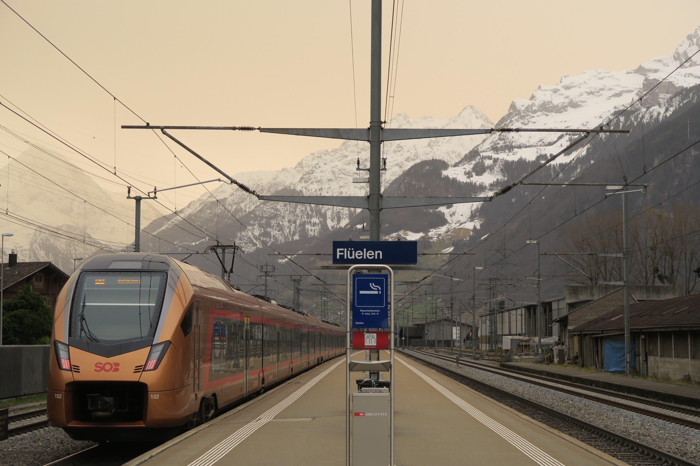Der abfahrende 12.15h-Treno Gottardo der SOB harmoniert am 6.2.2021 in Flüelen mit den Farben des einschwebenden Saharastaubes.