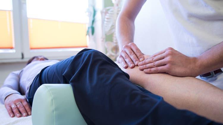 Ein Physiotherapeut bei der Behandlung einer Patientin. (Christin Klose / dpa Themendienst)