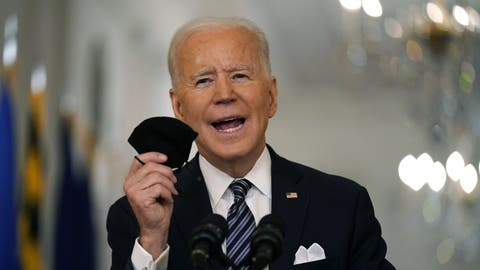 President Joe Biden holds up his face mask as he speaks about the COVID-19 pandemic during a prime-time address from the East Room of the White House, Thursday, March 11, 2021, in Washington. (AP Photo/Andrew Harnik)Joe Biden (Andrew Harnik / AP)