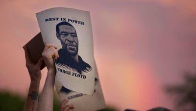 Demonstranten halten während eines Protestes Zettel mit dem Porträt von George Floyd in die Höhe. (Foto: Keystone)