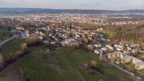 Im Vordergrund liegt das Land Rai, links das Zentrum Bergli mit Tankstelle und Volg, in der Mitte der Ortsteil Baltenschwil, rechts die Überbauung Honerethof, im Hintergrund Dietikon und das rechte Limmattal. (Bild: Severin Bigler)
