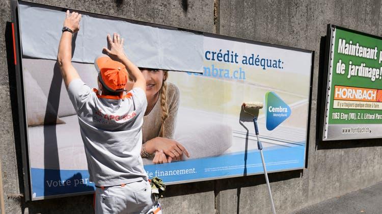 Ein APG-Mitarbeiter erneuert in Lausanne Plakate. Das Geschäft mit der Werbung im öffentlichen Raum litt stark unter der Coronapandemie. (Keystone)