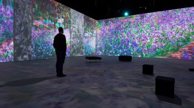 Impressionisten-Multimedia-Show in der Messe Luzern: Gemälde (hier Claude Monets «Der Garten des Künstlers in Giverny») werden rundum an bis zu 6 Meter hohe Leinwände projiziert. (Bild: Dominik Wunderli (Luzern, 16. März 2021))