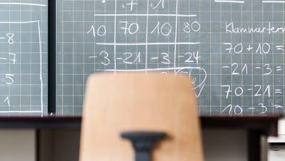 Corona hat den Schulalltag verändert: Eine beschriebene Wandtafel, eine Schulbank und ein Stuhl in einem leerenMathematikzimmer. (Bild: Christian Beutler/KEYSTONE)