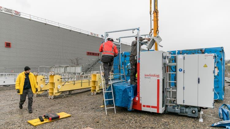 Schritt 1: Ein sogenanntes Lastaufnahmegerät - also das bewegliche Teil, das am Mast hochfährt und die Paletten aus den Regalen holt – wird am Boden an den Kran gehängt und zum Abheben bereit gemacht. (Sandra Ardizzone)