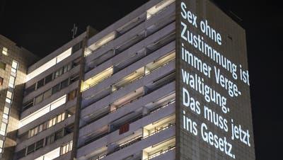 Aktivistinnen von Amnesty International projizieren eine Botschaft auf den Wohnblock Lochergut in Zürich. (Alexandra Wey / Keystone (Zürich, 7.3.2021))