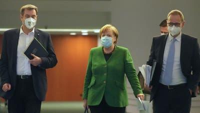 Auf dem Weg zur Pressekonferenz nach der Marathon-Sitzung: Kanzlerin Angela Merkel, CSU-Chef Markus Söder (links) und Berlins Regierender SPD-Bürgermeister Michael Müller (rechts). (Michael Kappeler / AP/23. März 2021)