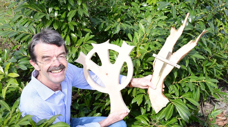 Peter Buchegger mit dem für den Rundgang geschaffenen Osterkreuz und einem Messingkreuz auf einem Rottannenstück. (Bild: Werner Lenzin)