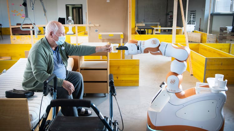 Noch ist es nur ein Test: Assistenzroboter Lioserviert Senior Hermann Dronski(85) im dritten Anlauf in einer Altstätter Industriehalle ein Getränk. (Bild: Ralph Ribi)