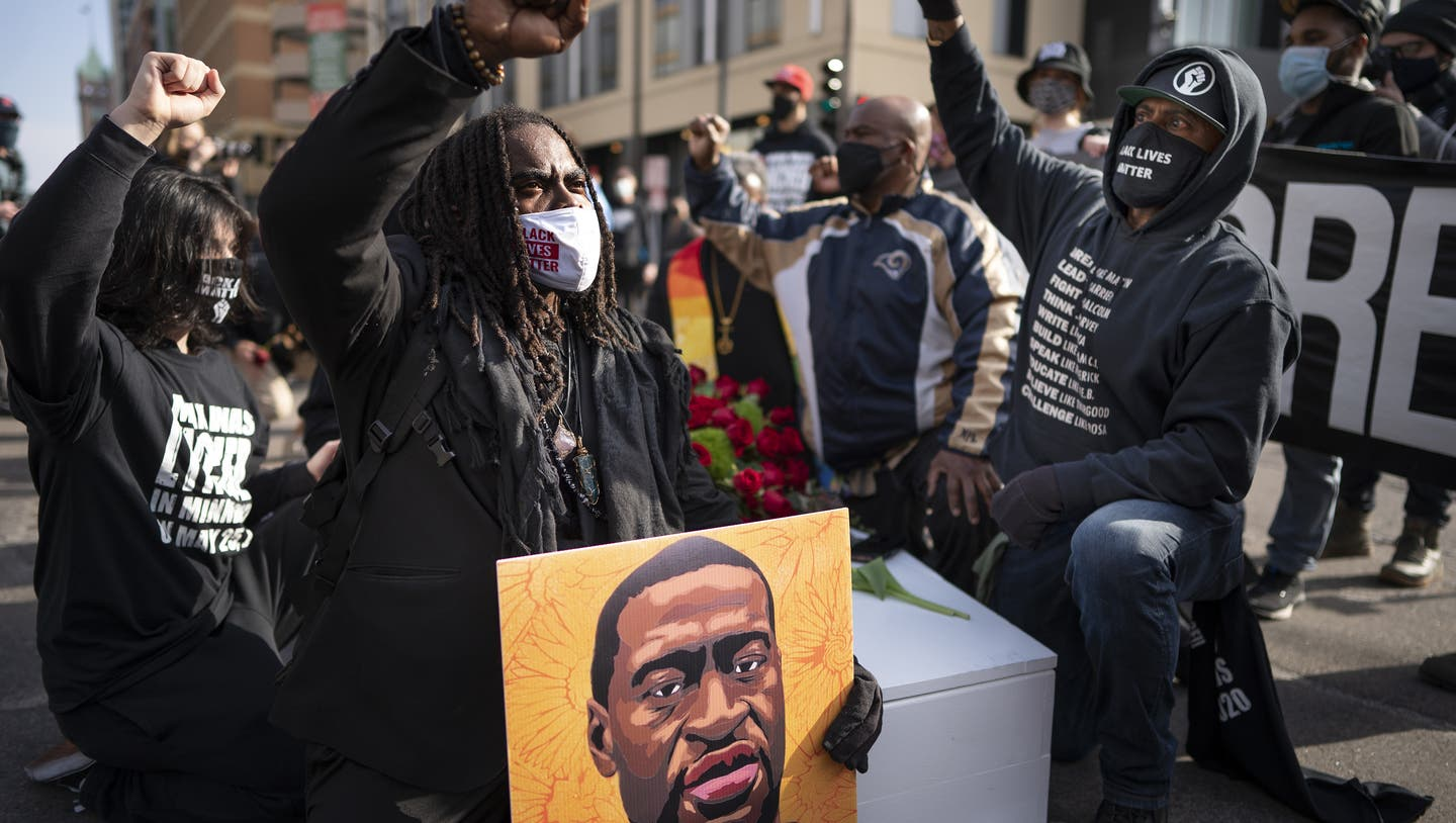 Cortez Rice, left, of Minneapolis, sits with others in the middle of Hennepin Avenue on Sunday, March 7, 2021, in Minneapolis, Minn., to mourn the death of George Floyd a day before jury selection is set to begin in the trial of former Minneapolis officer Derek Chauvin, who is charged in Floyd's death. (Jerry Holt/Star Tribune via AP) (Jerry Holt / AP)