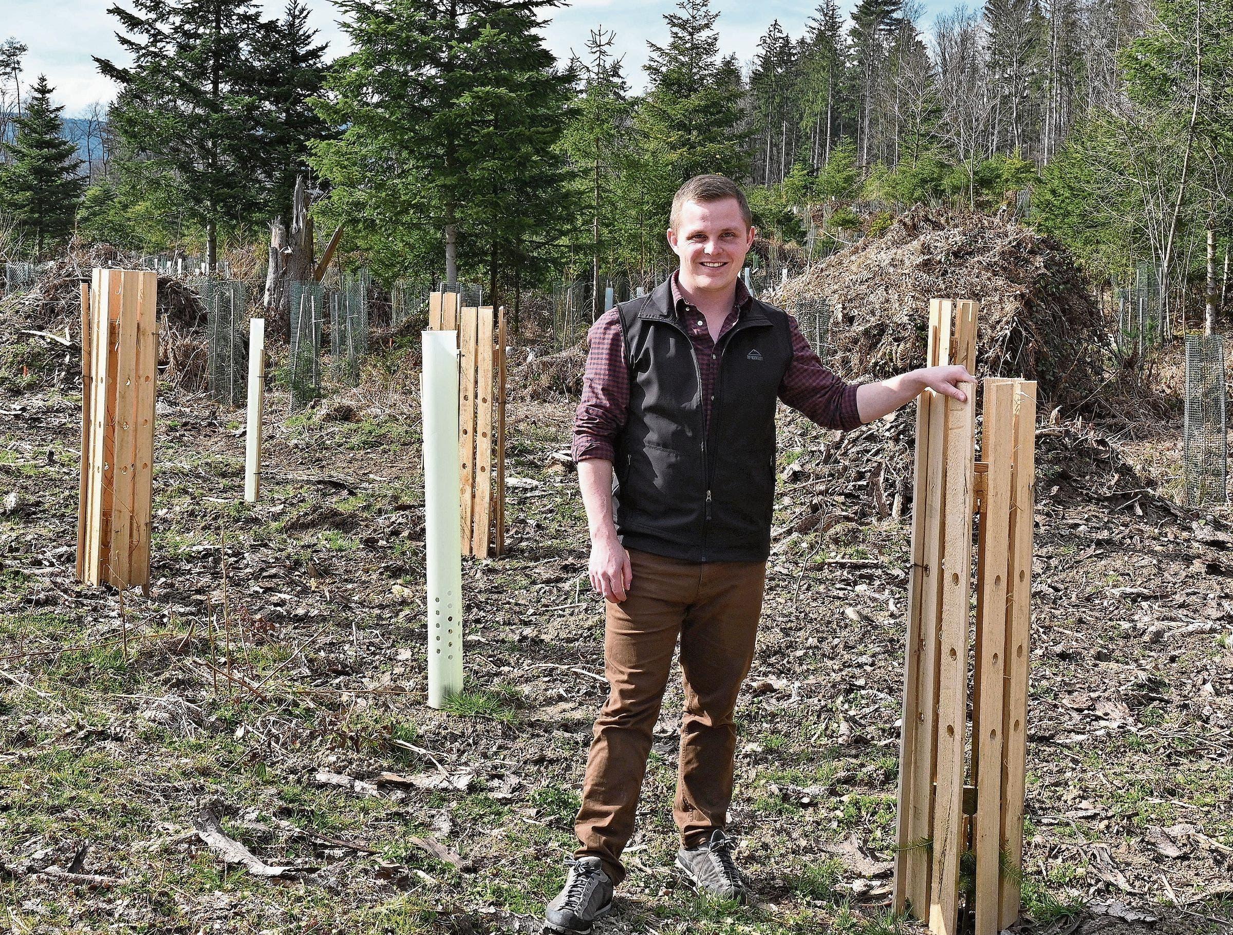 Joshua Huber steht neben einem jungen Baum. Das Holz dient als Schutz.