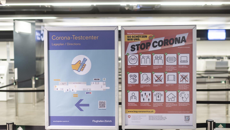 Plakate zeigen den Weg zum Covid-Test am Flughafen in Zürich. (Keystone)