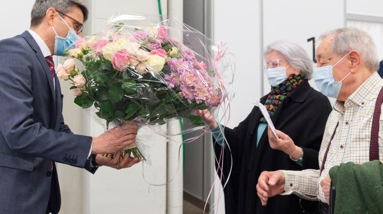 Regierungsrat Lukas Engelberger überreichte Blumen für Lina Arti– sie erhielt die 10'000. Impfung in Basel-Stadt. (Bild: zvg / Photo Basilisk)