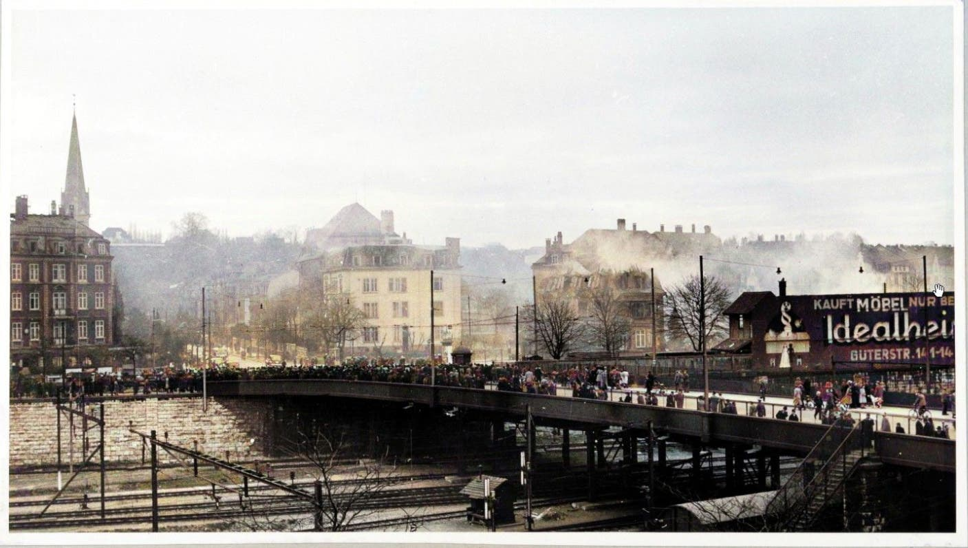 Bombardierung von Basel 4. März 1945: Auf der Münchensteinerbrücke strömen Schaulustige zusammen, aus den getroffenen Häuserzeilen an der Hoch- und Tellstrasse steigen Rauschwaden empor.