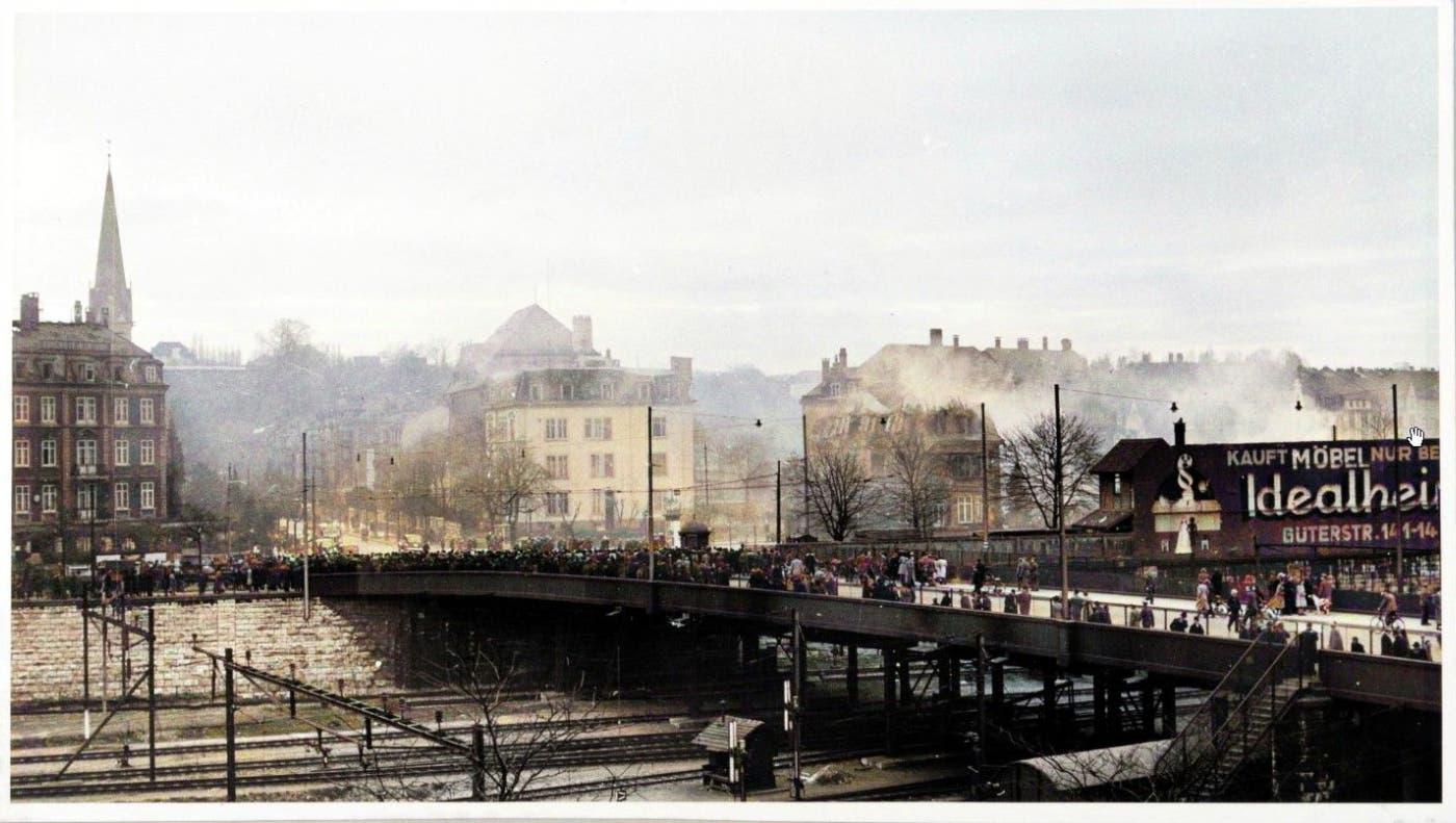 Bombardierung von Basel 4. März 1945: Auf der Münchensteinerbrücke strömen Schaulustige zusammen, aus den getroffenen Häuserzeilen an der Hoch- und Tellstrasse steigen Rauschwaden empor. (ZVG/Sammlung Patrick Schlenker, koloriert von Patrick Schlenker)