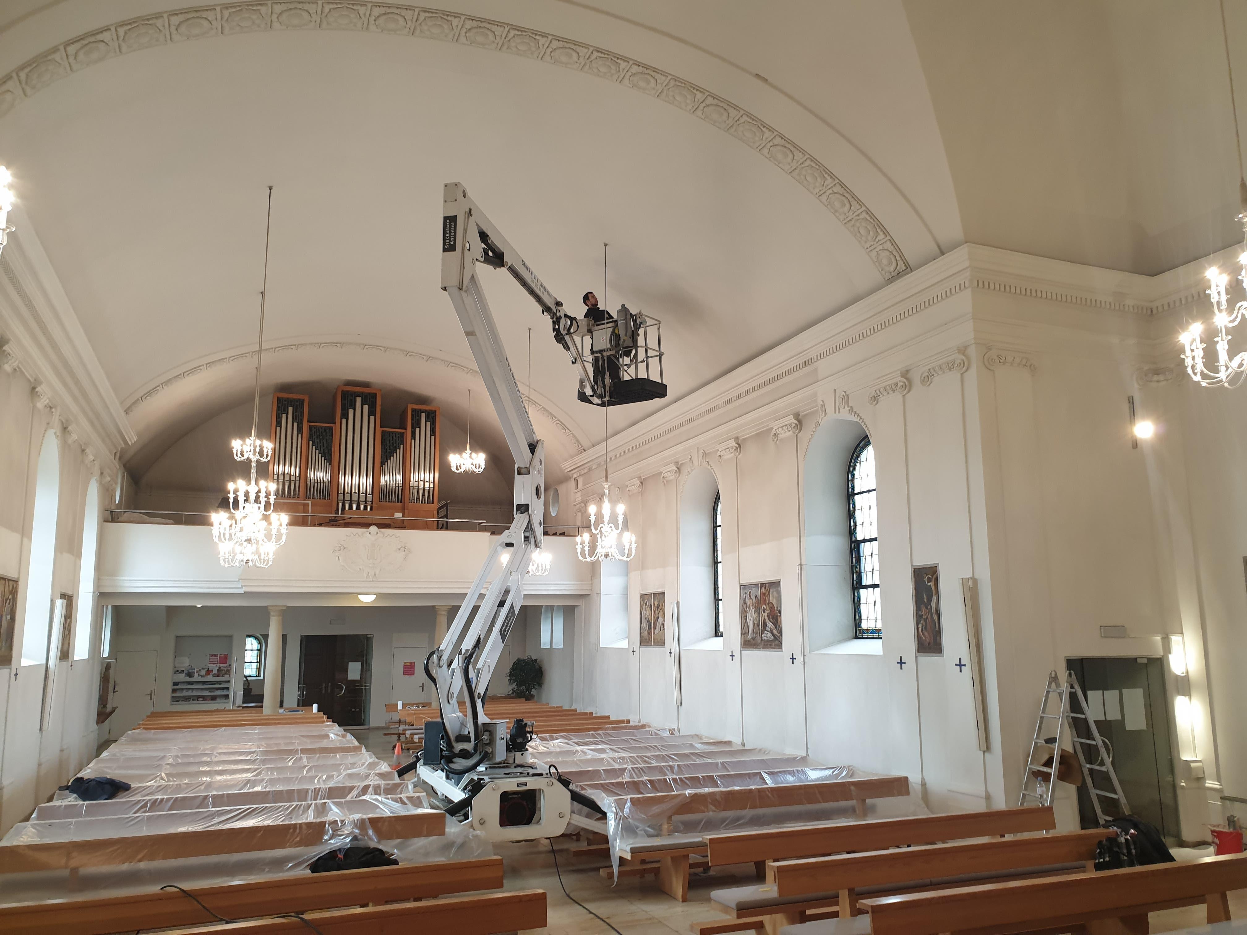 Dank einer umgebauten Hebebühne müssen keine Kirchenbänke demontiert werden. Die Mitarbeiter der Firma Stuckatura Antonini AG erreichen so jede Stelle in der Kirche.