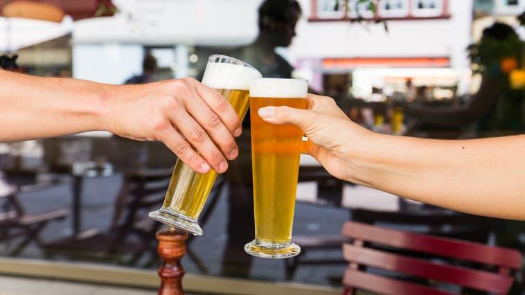 Derzeit noch nicht möglich: Zwei Personen prosten sich in einer Bar mit einem Glas Bier zu. (Bild: Severin Bigler)