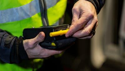 Ein Polizist führt bei einem Autofahrer eine Atem-Alkoholkontrolle durch. (Symbolbild: Severin Bigler)