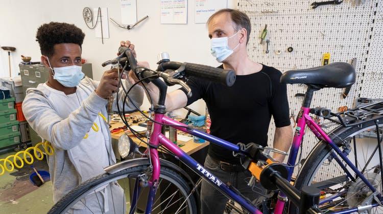Unter der Anleitung von Profi Martin Streicher repariert der geflüchtete Eritreer Negasi Girmay in der Velowerkstatt in Ennetbaden Fahrräder. (Bilder: Alex Spichale)