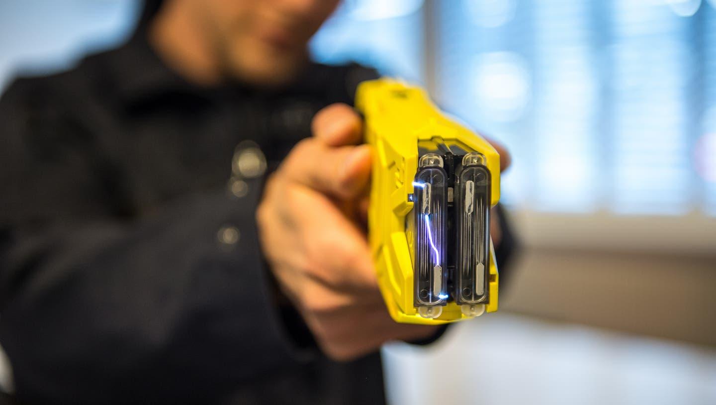 Ein Polizist führt einen Taser vor (Bild: Dominik Wunderli)