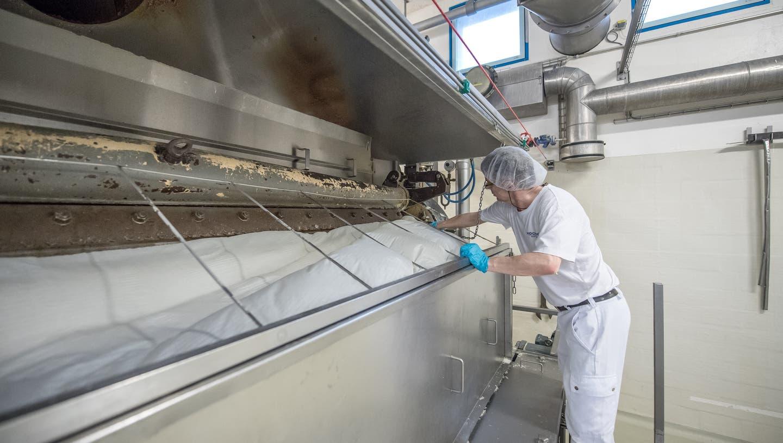 Blick in die Produktion des Milchverarbeiters Hochdorf. Auf dem Bild zu sehen ist ein Mitarbeiter bei einer Kontrolle der Walze, mit der Milchpulver hergestellt wird. ((Bild: Pius Amrein, 19. Dezember 2019))