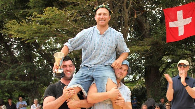 Erwin Hebler, der neuseeländische «Schwingerkönig» wird von seinen Konkurrenten gefeiert. Rechts applaudiert Michael Winzap, der Schweizer Botschafter in Neuseeland. (Bild: Matthias Stadler (Kaponga, 14. Februar 2021))