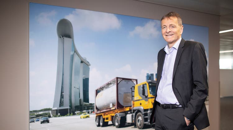 Hans-Jörg Bertschi vor einem Foto, das die Globalisierung seines Unternehmenssymbolisiert: Typisch gelber Bertschi-Lastwagen braust am Luxushotel Marina Bay Sands in Singapur vorbei. (Britta Gut)