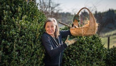 Ab durch die Hecke. Monika Pearson bringt Gerät für die Arbeit im Beet. (Bild: Michel Canonica)