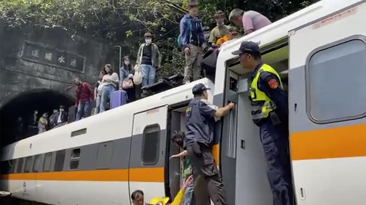 In this photo released by National Fire Agency, rescue workers are seen near the site of a partial train derailment in Toroko Gorge in Taiwan's eastern Hualien region, Friday, April 2, 2021. The train partially derailed along Taiwan's east coast Friday, injuring an unknown number of passengers and causing potential fatalities. (National Fire Agency Department via AP) (AP)