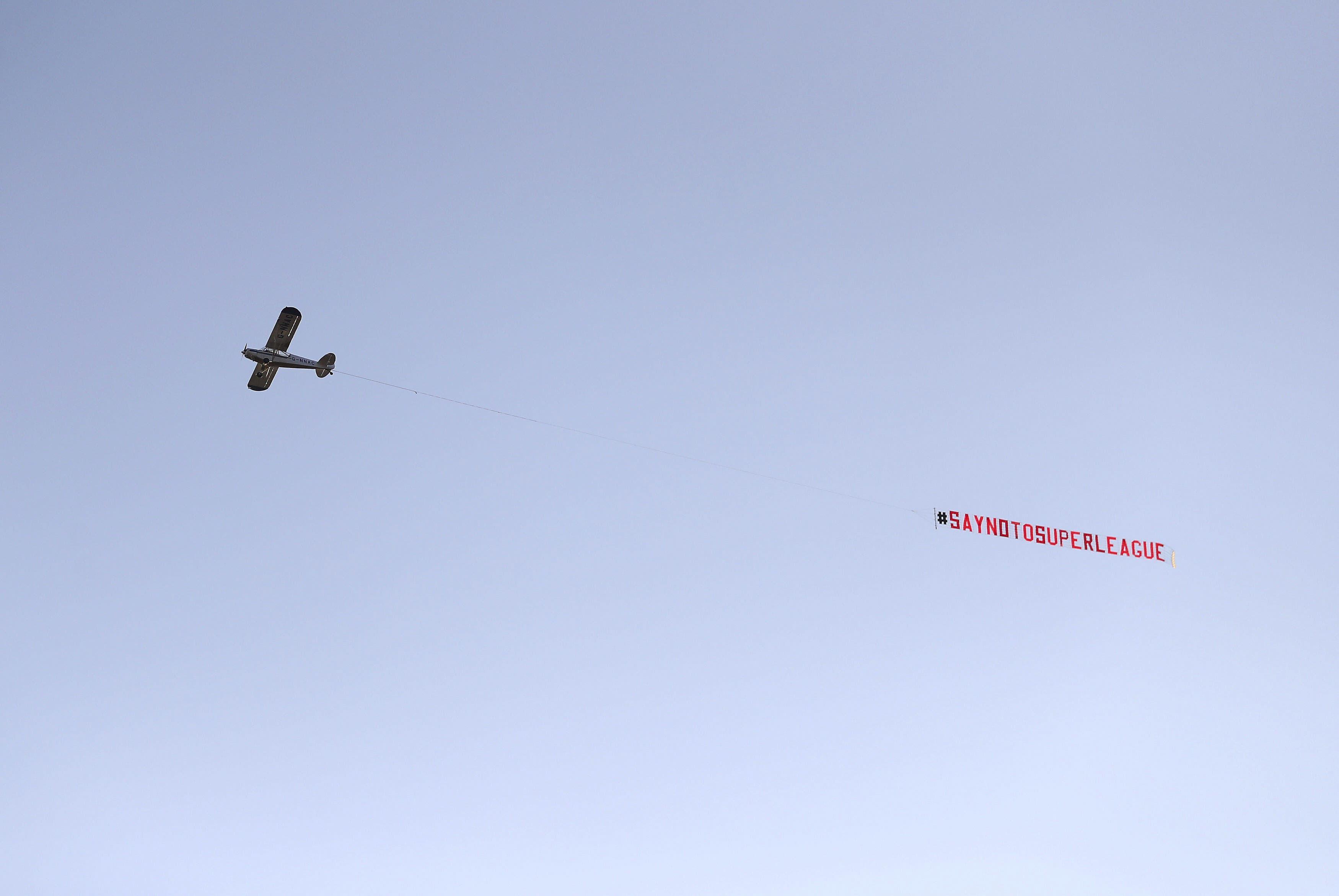 """Ein Flugezeug mit einem """"Sagt nein zur Super League""""-Banner fliegt vor der Partie über das Stadion."""