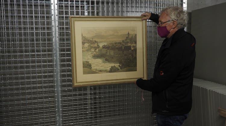 Hannes Burger, Präsident Museumsverein Laufenburg, hängt das erste Bild im neuen Archiv in der Zivilschutzanlage Rheinsulz auf, (Thomas Wehrli / Aargauer Zeitung)