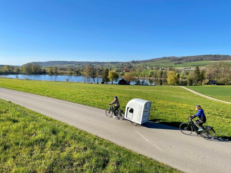 Der Velovan bietet mit seiner 90er Matratze Platz für bis zu zwei Personen. Er ist zudem mit einem Vorzelt, Campingstühlen und Tisch ausgestattet.