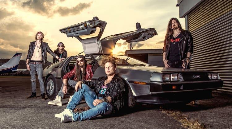 Melodic-Rock hat es ihm angetan: Marco Troxler, Gitarrist der Band Fighter V, hinter einemDMC DeLorean auf. Das vielleicht ikonischste Auto der 80er-Jahre steht hier für die unüberseh- und -hörbare Botschaft der Rockband: «Mit voller Kraft zurück in die 80er.» (Bild: PD/Fighter V)