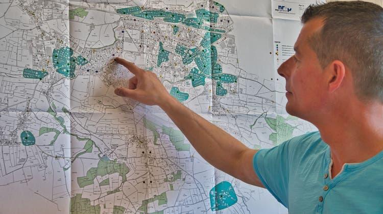 Joachim Düring von der Bauverwaltung der Stadt schaut auf die Karte des Gemeindegebiets mit bestehenden (grüne Punkte) und geplanten Unterflurcontainern. Die türkis eingefärbten Gebiete, in denen sich die grünen Punkte befinden, gelten als abgedeckt. (Bild: Manuel Nagel (Amriswil, 31. März 2021))