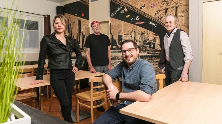 Aline Studer, Claudio Eckmann (rechts) und Kevin Kofel (sitzend) zeigen mit Rolf Kellenberger, dem Wirt des Bistro Ampère, die spezielle Tapete im Hintergrund. (Sandra Ardizzone)