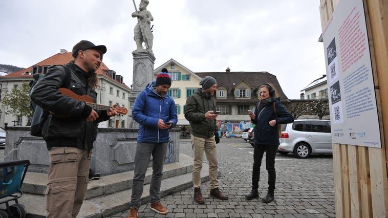 Dorfplatz Stans: Die ersten Besucherinnen und Besucher der Stanser Musiktage versuchen es mit dem Podcast zum Audiowalk. (Bild: Urs Hanhart (7. April 2021))